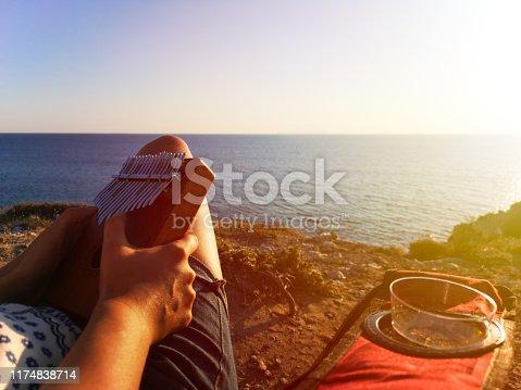Kalimba expert musician player playing muscial instrument at seaside sunset