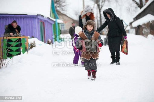 Belarus, the city of Gomil, January 13, 2019. Rite of a generous evening. Kalyada ceremony. A village child with a Russian accordion walks along a winter road