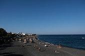 People relaxing on the beach in Kamari beach, Santorini, Greece on August 12, 2020