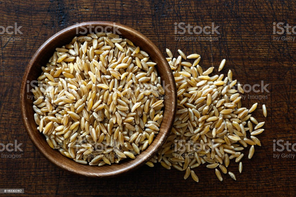 Kamut wheat kernels in dark wooden bowl isolated on dark brown wood from above. Spilled wheat. stock photo