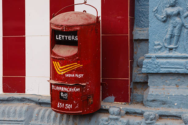Kanchipuram, India: An Old Style Hand Painted India Postal Service Post Box Hung On A Temple Wall. The Dusty Red Box Indicates When It Will Be Cleared Next stock photo