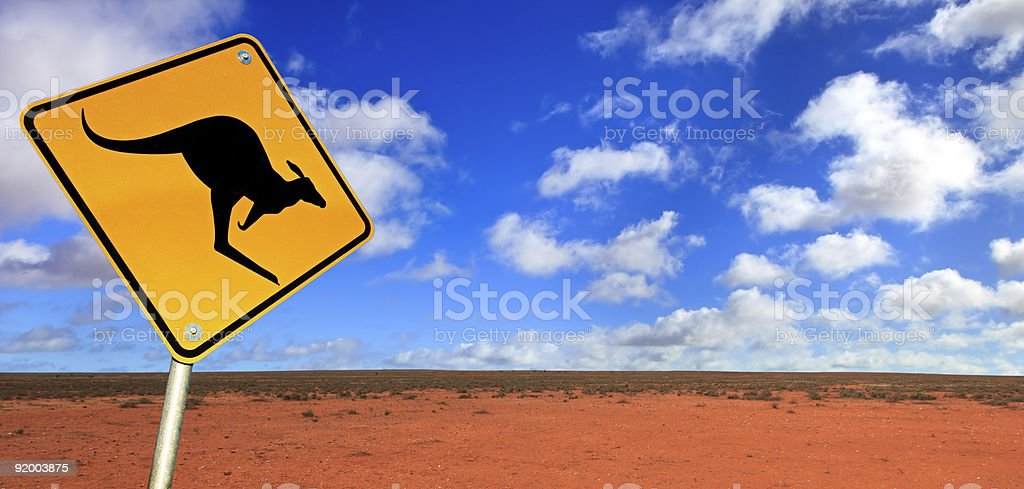 Kangaroo warning sign with blue sky and red earth stock photo