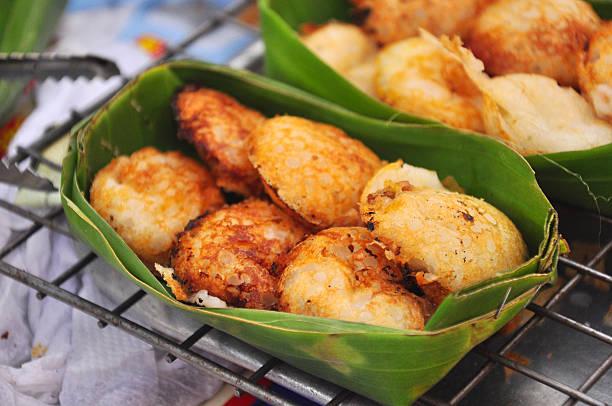 kanom krok, dessert thailändisch. thailändischer kokosnuss-pudding auf banane verlassen - kokoskuchen stock-fotos und bilder
