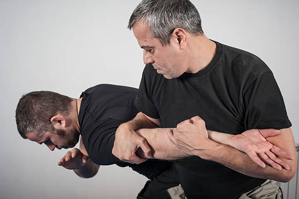Kapap instructor demonstrates arm bar techniques Kapap instructor demonstrates arm bar techniques with his student self defense stock pictures, royalty-free photos & images