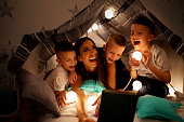 Children  in homemade tent at home having fun with mother