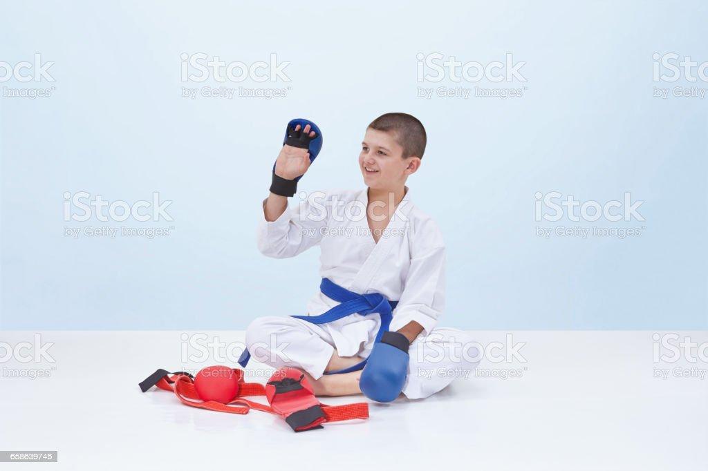 Karate boy in karategi raised his hand in greeting stock photo istock karate boy in karategi raised his hand in greeting royalty free stock photo m4hsunfo