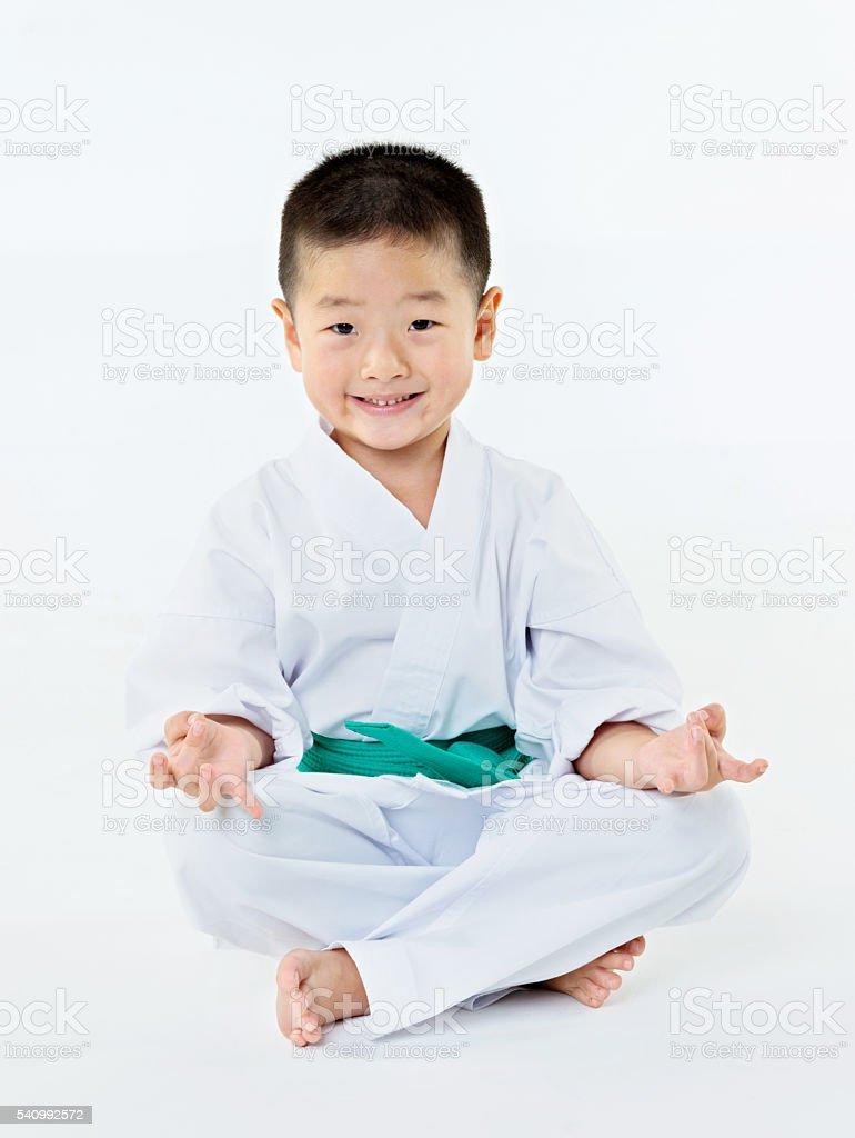 Карате мальчик сидит на полу стоковое фото