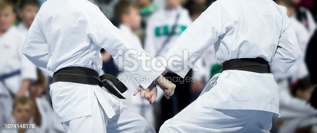 karate do kids fight on blur background. Sport competition