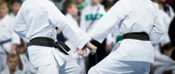 los niños de hacer karate luchan desenfoque de fondo. competiciones deportivas - kárate fotografías e imágenes de stock