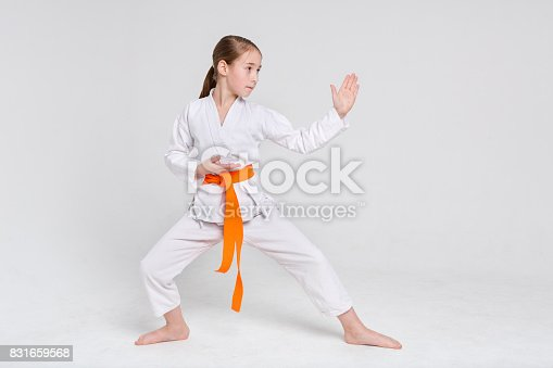 istock Karate girl in kimono in stand at studio background 831659568