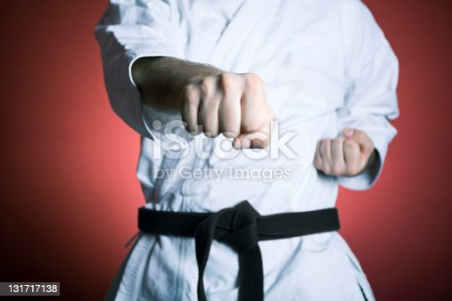 Young man practicing karate over red background. See more