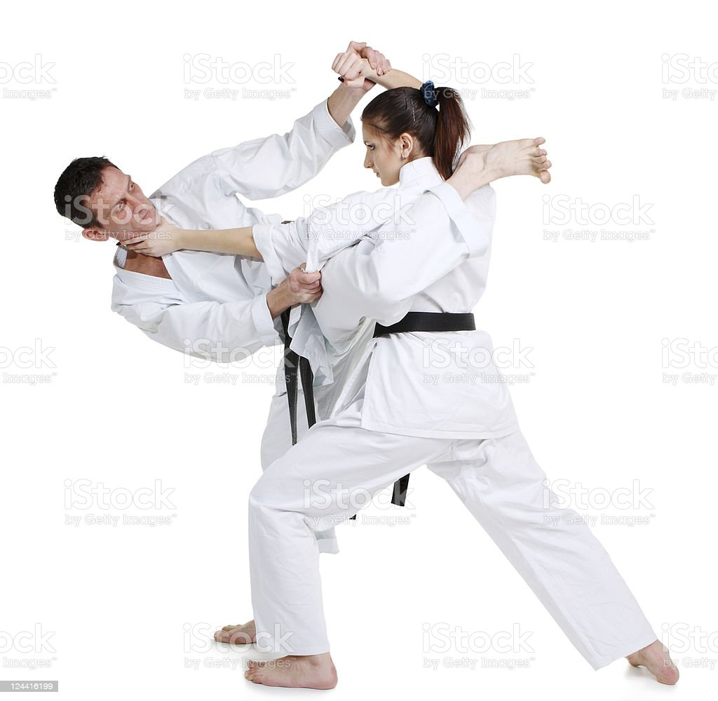 Karate. Young girl and a men in a kimono with a white background....