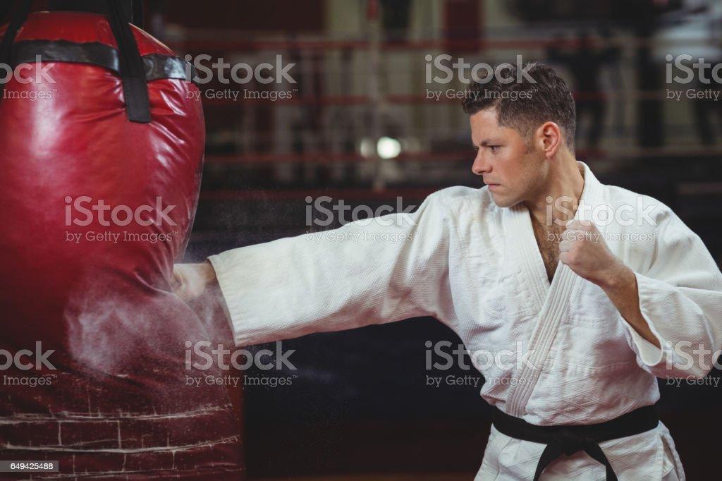 Jugador Karate practicando karate con saco de boxeo - foto de stock