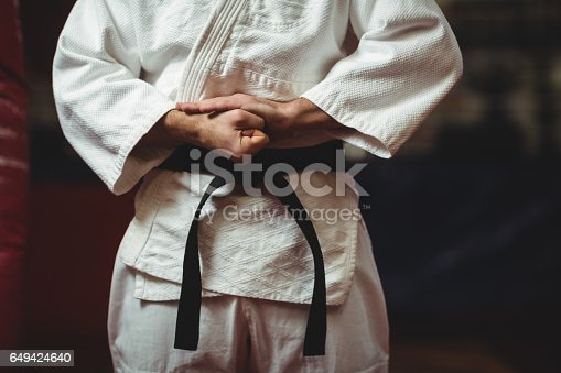 Mid section of karate player tying his belt in fitness studio