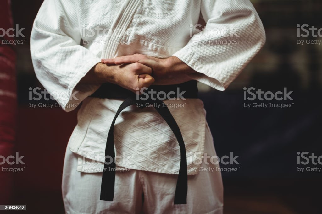 Karate player tying his belt stock photo