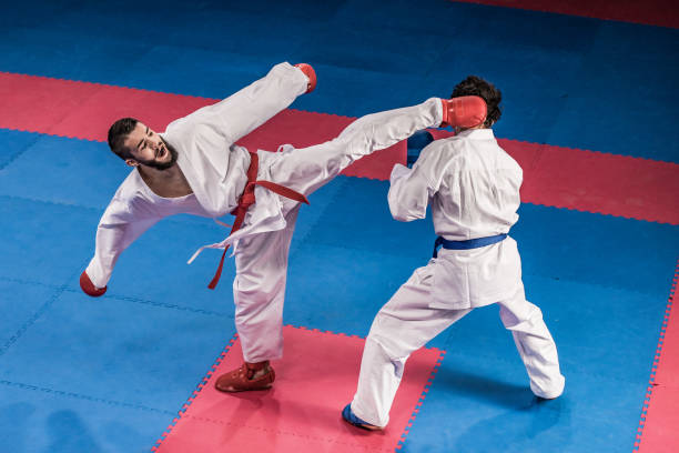 Karate players competing during the match Male karate players fighting during the competition. karate stock pictures, royalty-free photos & images