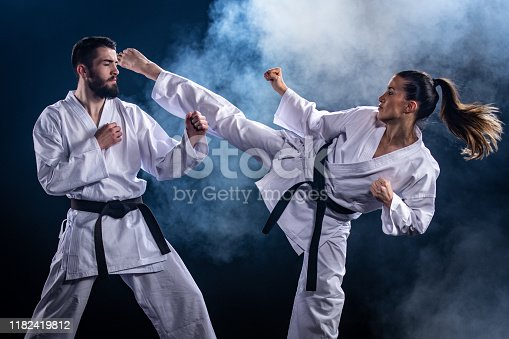 Male and female karate players fighting during competition against blue background.
