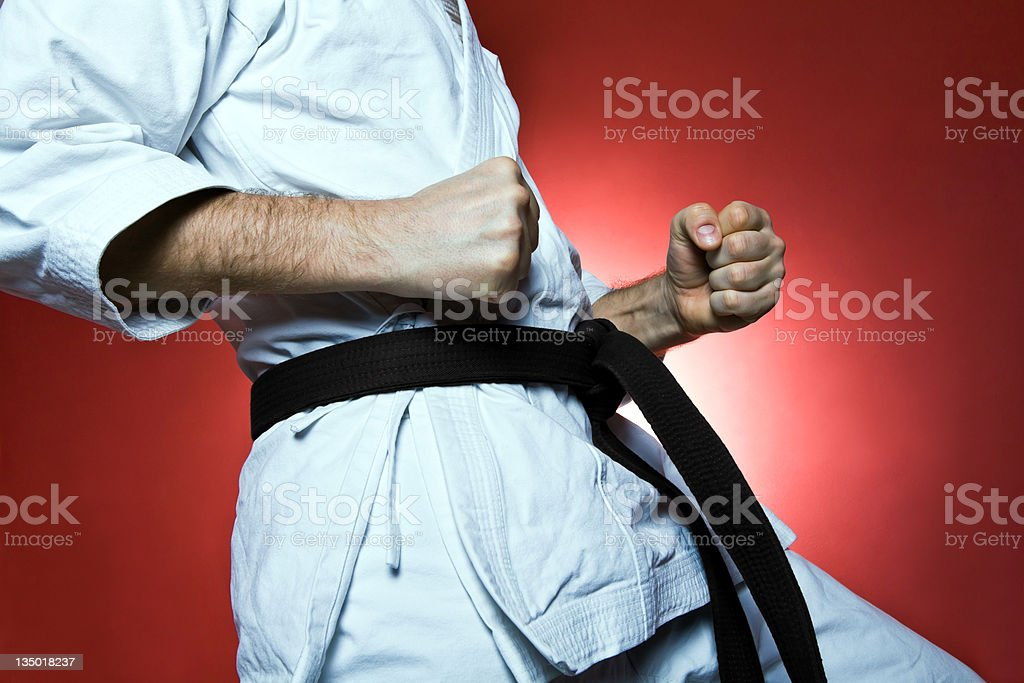 Young man training karate over red background. Please see more