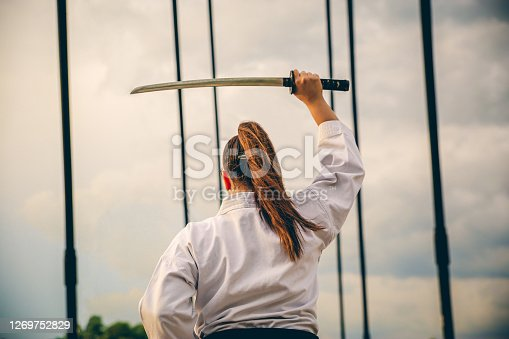 Young caucasian karate woman holding sword outdoor