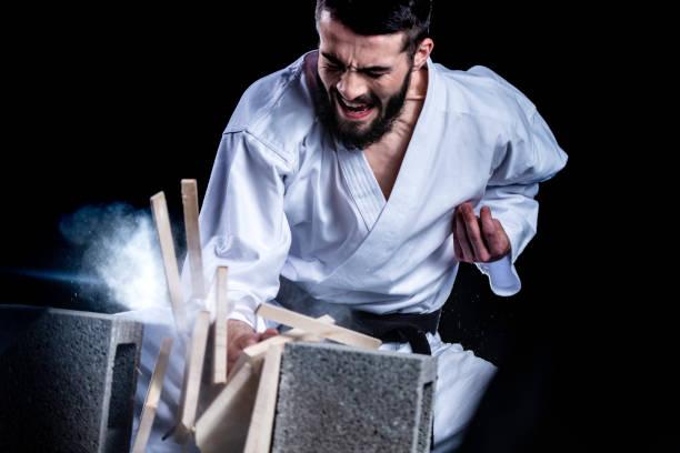 Karateka bricht mit der Hand ein Holzbrett – Foto