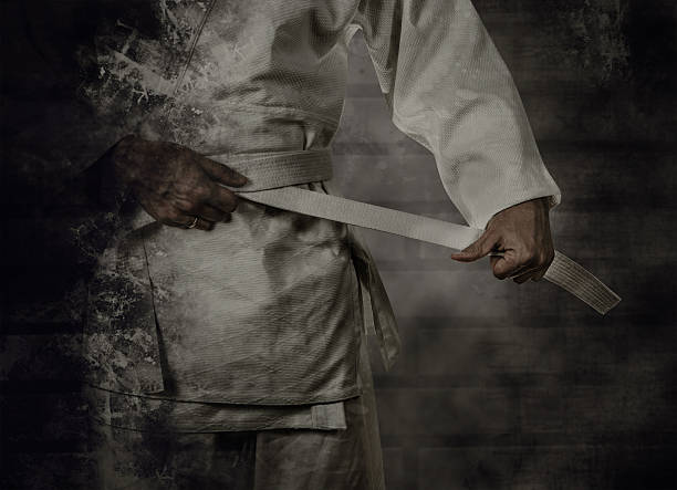 Karateka tying the white belt (obi) with grunge background stock photo