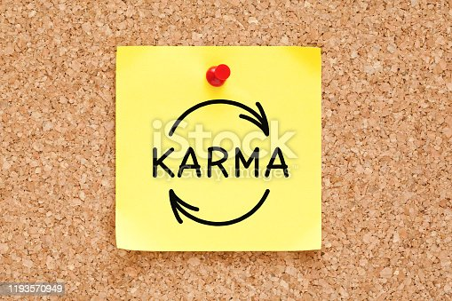 Hand drawing Karma cycle concept on yellow adhesive note pinned on cork bulletin board.