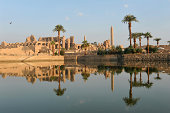 'The Ancient Egyptian temple of Karnak illuminated by and reflecting the golden light of early morningLuxor, Egypt'