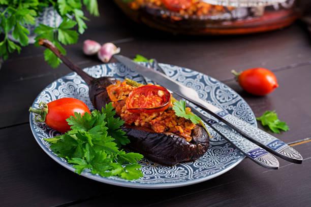 Karniyarik - türkische traditionelle Aubergine Auberginen Auberginen Mahlzeit. Gefüllte Auberginen mit gemahlenem Rindfleisch und Gemüse mit Tomatensauce gebacken. Türkische Küche. – Foto