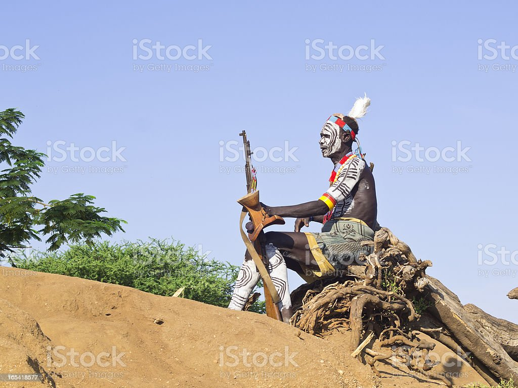 Karros tribesman posing sitting on sticks royalty-free stock photo