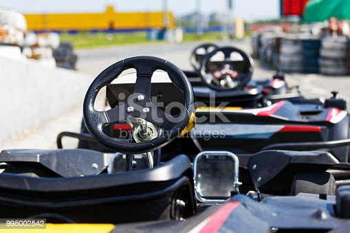 Kart cars parked next to track in anticipation of drivers. Shallow focus.