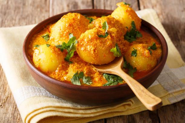 Kashmiri dum aloo: spicy potato with sauce closeup on the plate. Horizontal stock photo