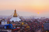 Kathmandu city view on the early morning on sunrise with rising sun and famous buddhist Boudhanath Stupa temple. Tibetan traditional architecture, Nepal.