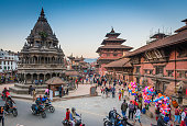 Kathmandu, Nepal - November 7, 2016: Clear blue skies over the wooden temples and shrines as crowds of visitors pass the historic monuments of Patan Durbar Square, a UNESCO World Heritage Site in the heart of Kathmandu, Nepal's vibrant capital city.