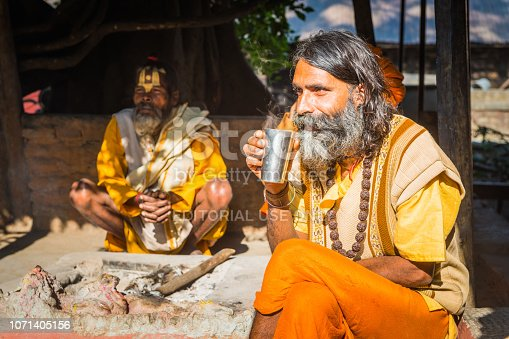 Group of Hindu sadhu holy men in their distinctive saffron robes sat around a dhuni fireplace in the courtyard of a crumbling temple in Kathmandu, Nepal's vibrant capital city.