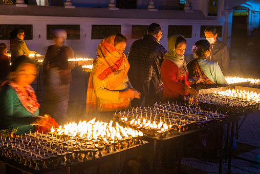 Women selling devotional butter lamps at night beside the huge stupa of Boudhanath temple in the heart of Kathmandu, Nepal's vibrant capital city.