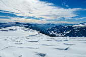 A panoramic view on snow capped Alps in Austria, seen from Katschberg Ski Resort in Austria.The slopes are covered with fresh, powder snow. Idyllic winter landscape. Sunny day