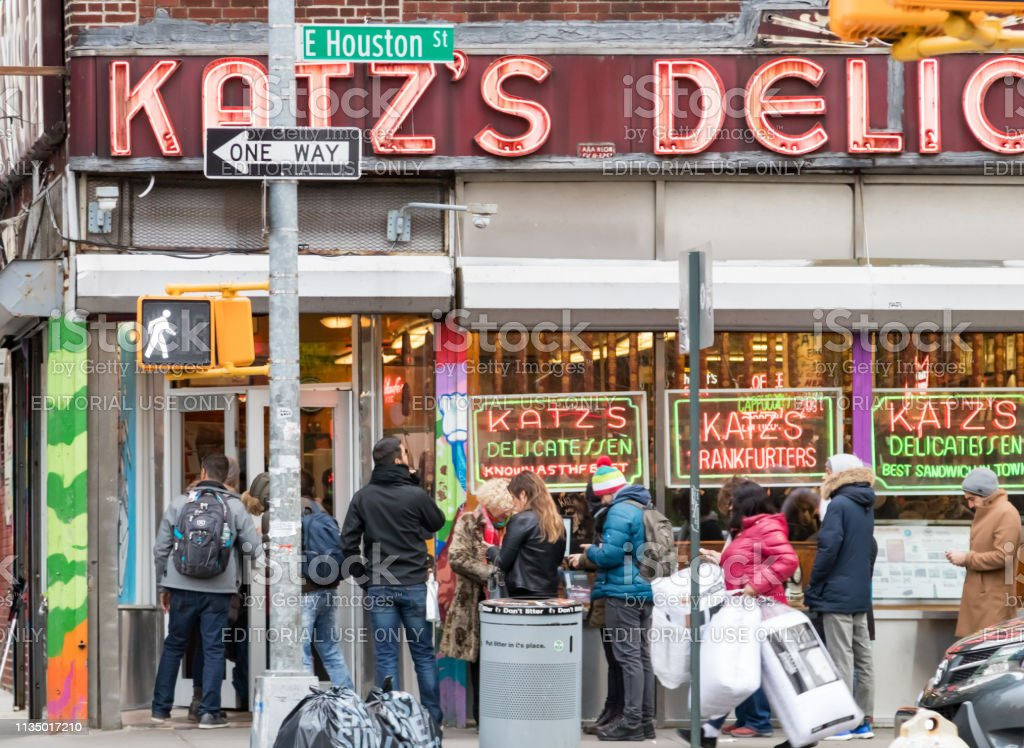 Katz's Deli in the Lower East Side of Manhattan in New York City NEW YORK CITY - CIRCA 2018: A crowd of people wait in line outside the famous Katz's Deli in the Lower East Side of Manhattan on Houston Street. Built Structure Stock Photo