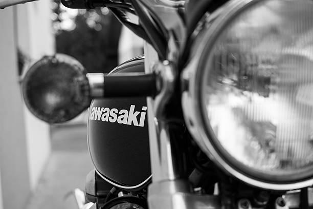Kawasaki motorcycle parked in the backyard Subotica, Serbia - Jun 13, 2015: Photo shoot of Kawasaki ZR 1100 Zephyr A1 bike from 1992, close up shoot of front light, handle and badge on reservoir. Four stroke transverse four cylinder,1062cc, air cooled. Black and white photo. Photographed in the family house backyard in Subotica, Serbia. Selective focus on badge Kawasaki. kawasaki heavy industries stock pictures, royalty-free photos & images
