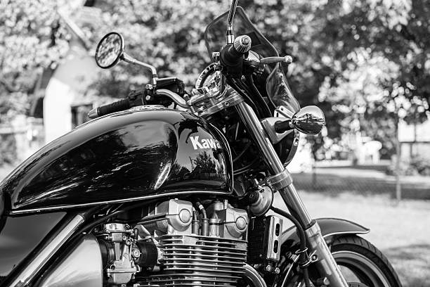 Kawasaki motorcycle parked in the backyard Subotica, Serbia - Jun 13, 2015: Photo shoot of Kawasaki ZR 1100 Zephyr A1 bike from 1992, close up shoot of front of a bike and chrome parts.1062cc. Selective focus: badge Four stroke transverse four cylinder,1062cc, air cooled. Black and white photo. Photographed in the family house backyard in Subotica, Serbia. kawasaki heavy industries stock pictures, royalty-free photos & images
