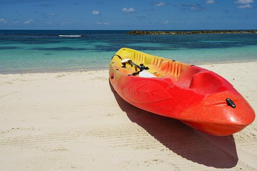 Kayak and paddle by the seashore on the beautiful white sand of Labadee, Haiti.