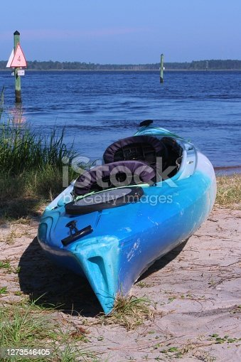 A blue kayak sitting on the beach at the Carolina Beach State Park