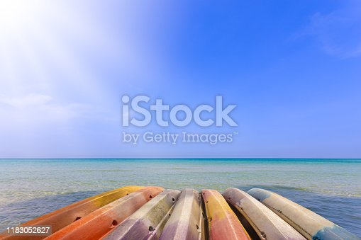old and colorful kayak boats beside sea, blue sky and sun ray, summer activity concept background
