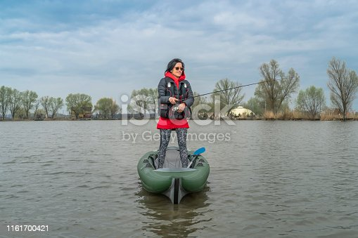 istock Kayak fishing at lake. Fisherwoman on inflatable boat with fishing tackle. 1161700421