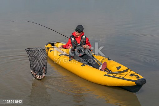 914030378istockphoto Kayak fishing at lake. Fisherwoman with pike fish on inflatable boat with fishing tackle. 1158541842