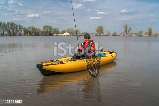 914030378istockphoto Kayak fishing at lake. Fisherwoman with pike fish on inflatable boat with fishing tackle. 1158541852