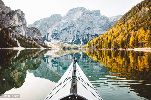 Beautiful view of kayak on a calm lake with amazing reflections of mountain peaks and trees with yellow autumn foliage in fall, Lago di Braies, Italy