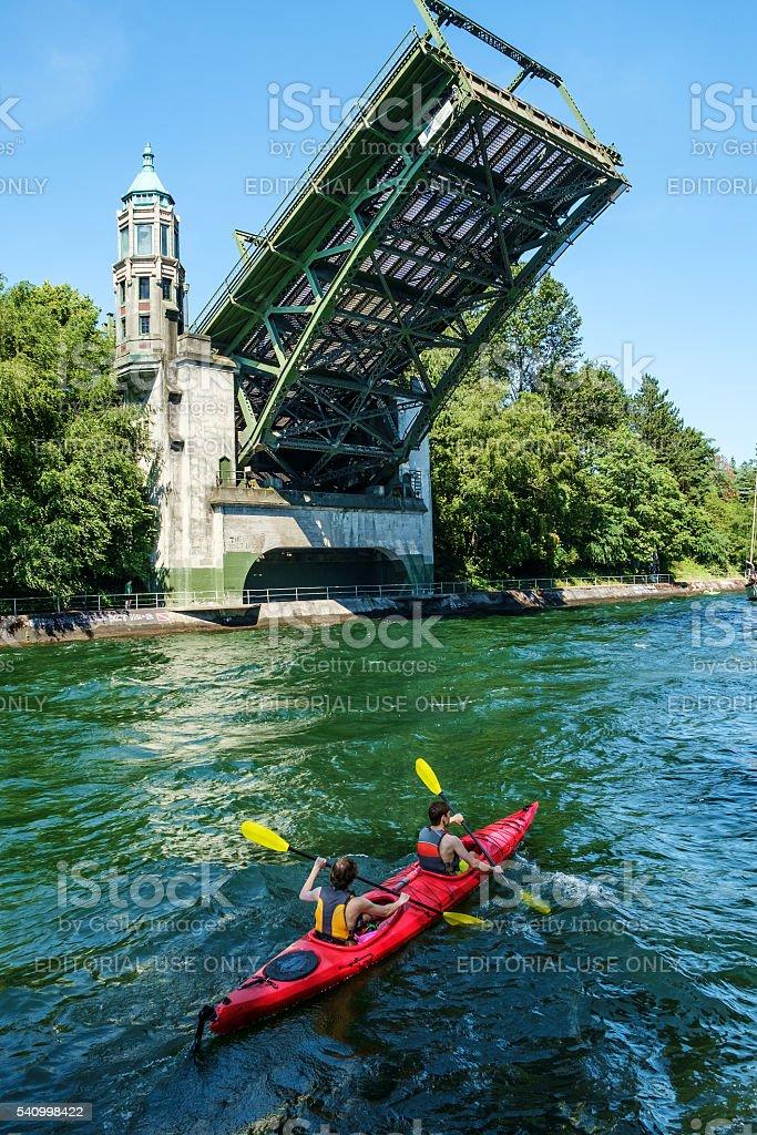 Kayak paddlers below open Montlake drawbridge stock photo