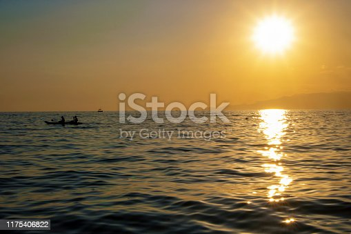 silhouette of a couple kayaking at sunset  in the sea of Maratea, Basilicata, Italy