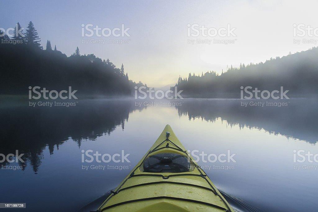 Kayak surfer on a  misty lake stock photo