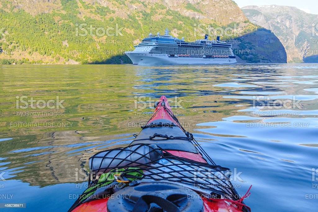 Kayak vs Cruise ship stock photo